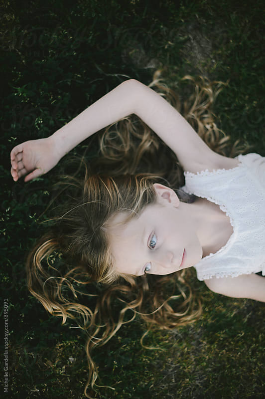 Girl Laying in a Clover Field  by Michelle Gardella for Stocksy United