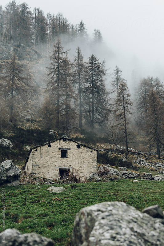 Traditional stones cabin of Alps into the foggy forest by Jordi Rulló for Stocksy United