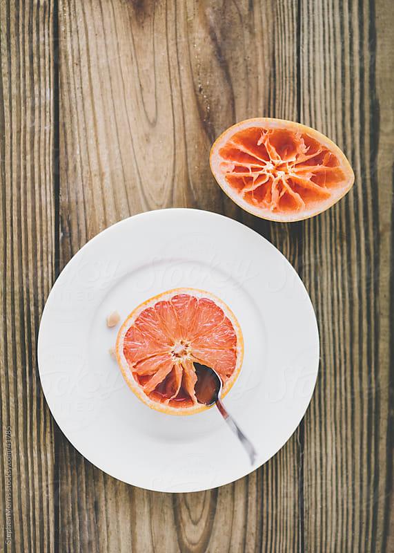 Half Eaten Grapefruit on Wood Table by Stephen Morris for Stocksy United