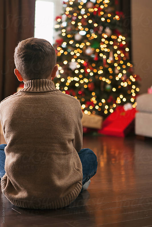 Christmas: Boy Sits On Floor Looking At Christmas Presents by Sean Locke for Stocksy United