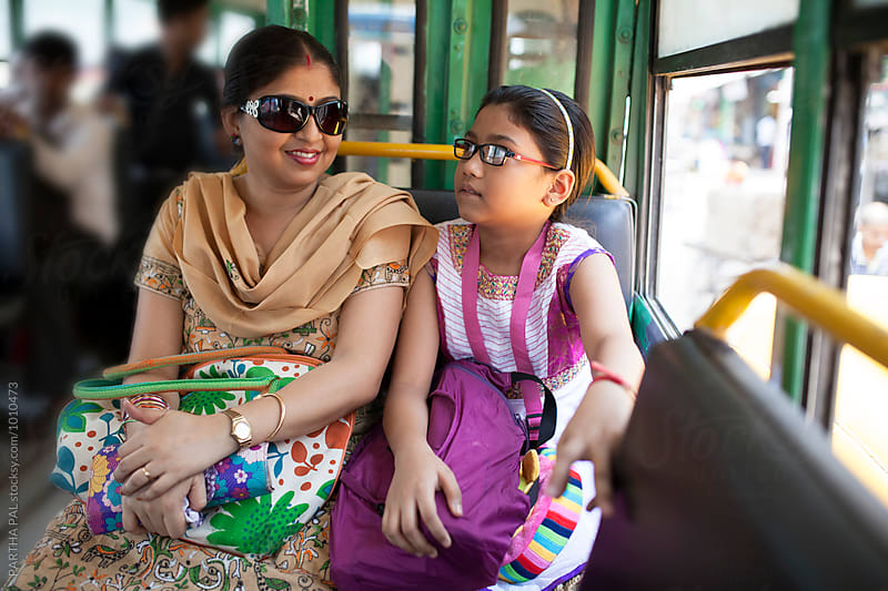 Mother and daughter travelling in a local Bus by PARTHA PAL for Stocksy United