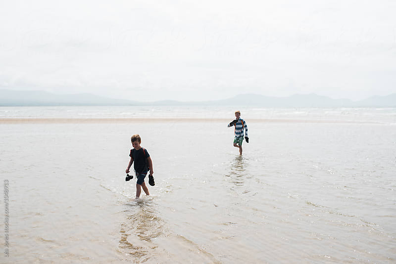 boys walking on beach by Léa Jones for Stocksy United