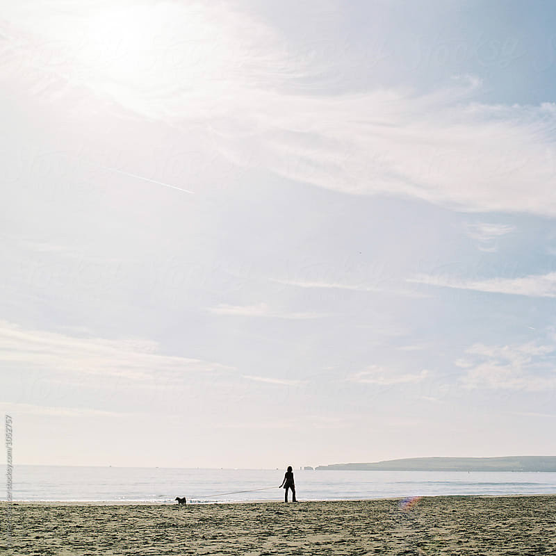 Woman walking her dog on the beach by Andrew Spencer for Stocksy United