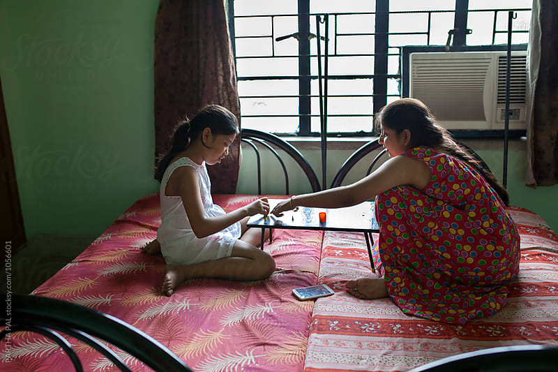 Daughter palying LUDO with mother by PARTHA PAL for Stocksy United