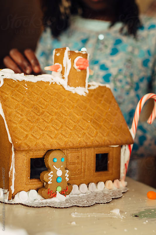 Black girl building a gingerbread house by Gabriel (Gabi) Bucataru for Stocksy United