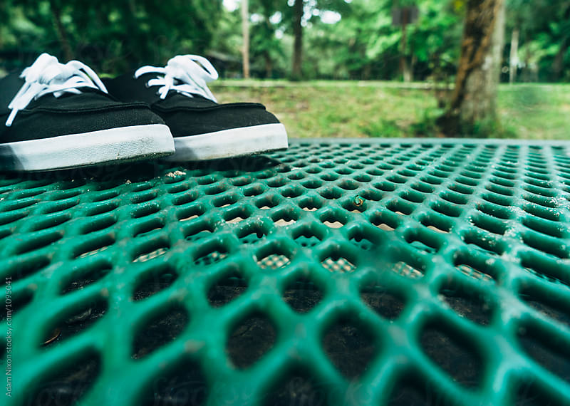Black sneakers on a green picnic table by Adam Nixon for Stocksy United