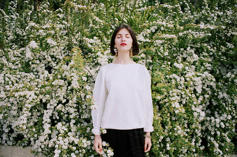 Young woman with close eyes standing among blossom by Lyuba Burakova for Stocksy United