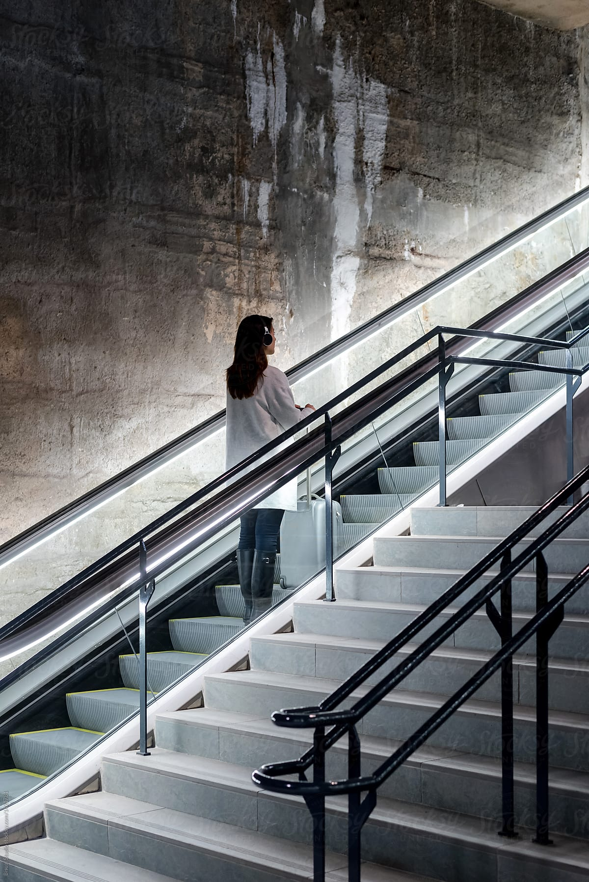Superieur Female Traveler In Headphones On Moving Stairs By Bisual Studio For Stocksy  United