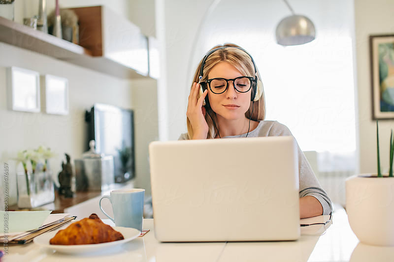 Woman using a Laptop with Headphones at Home by VICTOR TORRES for Stocksy United