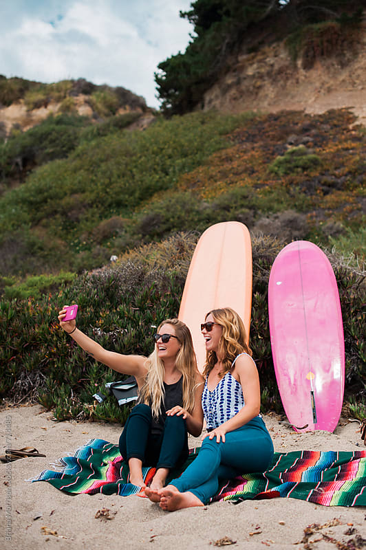Two Young Woman Sitting on the Beach Taking Selfie Photographs by Briana Morrison for Stocksy United