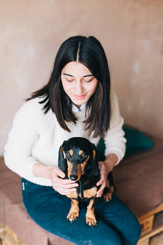 Woman with her dog indoor by VeaVea for Stocksy United