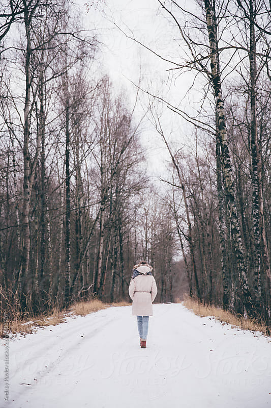 Girl goes on a snowy road by Andrey Pavlov for Stocksy United