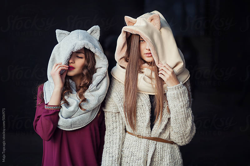 Two girls with cat hats laughing on a black background by Maja Topcagic for Stocksy United