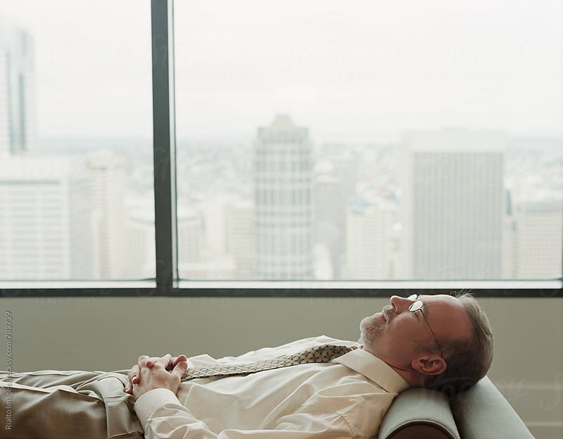 Business executive taking nap on office couch by Paul Edmondson for Stocksy United