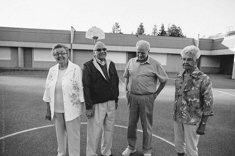 Funny portrait of grumpy caucasian seniors outside at schoolyard basketball courts by Rob and Julia Campbell for Stocksy United