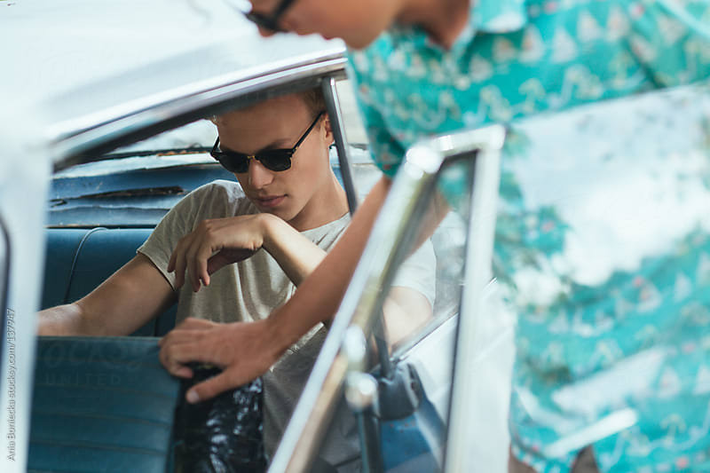 Two boys hanging out at a blue car by Ania Boniecka for Stocksy United