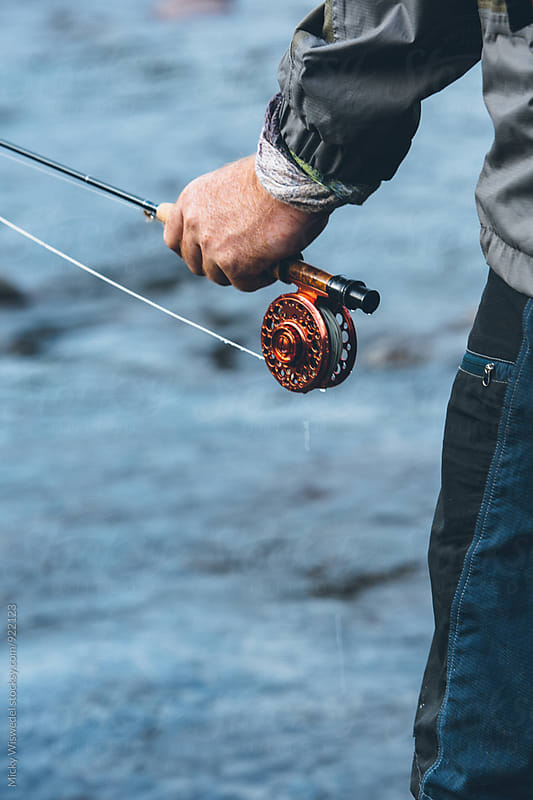 closeup od hands, reel and rod of a fly fisherman by Micky Wiswedel for Stocksy United