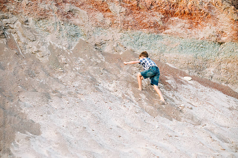 Boy climbs up a colorful sandy rock face by Rebecca Spencer for Stocksy United