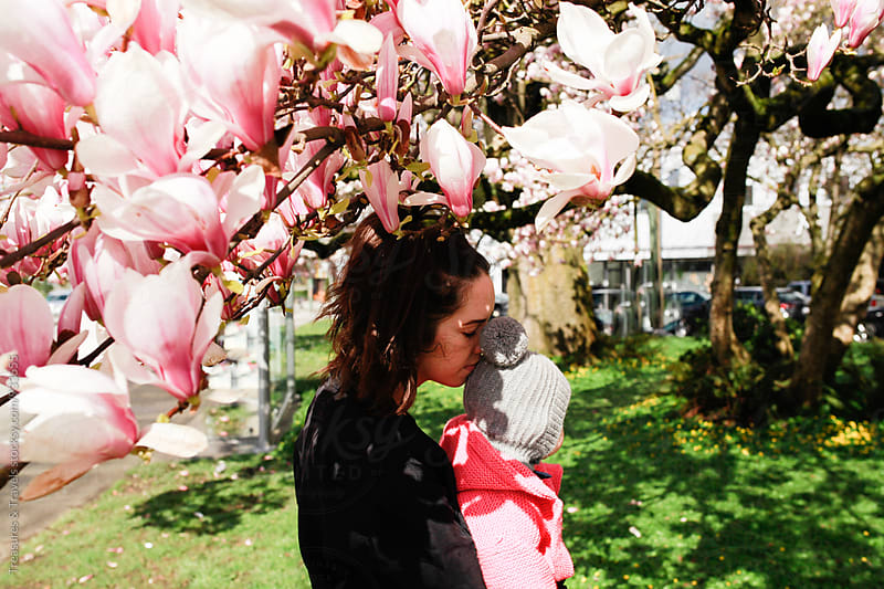 Young woman holding baby under spring blossoms by Treasures & Travels for Stocksy United