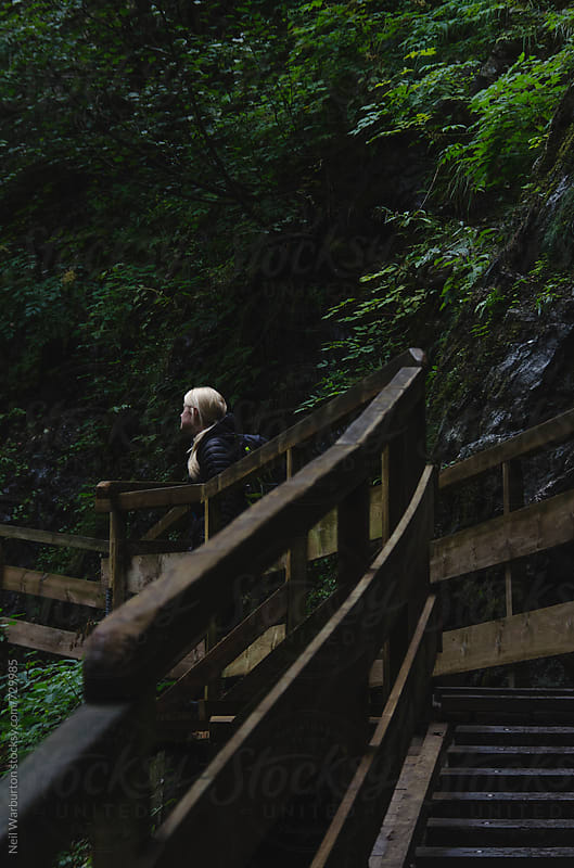 Young Woman looking from wooden walkway in a gorge by Neil Warburton for Stocksy United