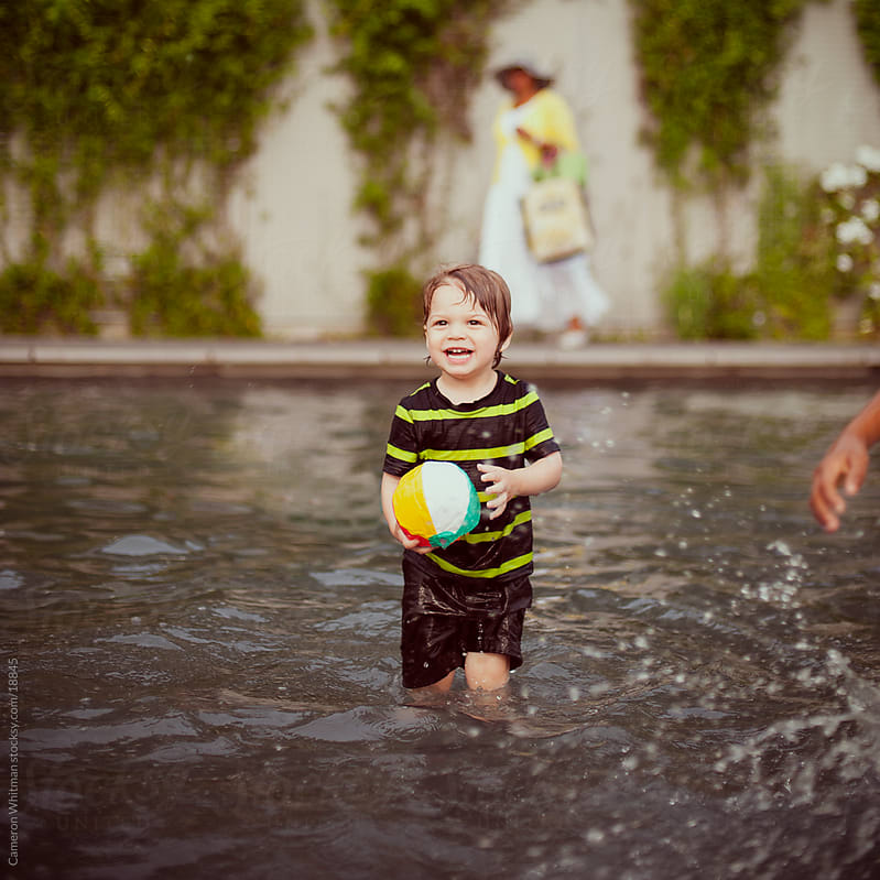 Child In Wading Pool, Summer Fun by Cameron Whitman for Stocksy United