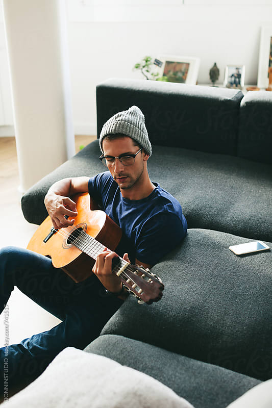 Young hipster man playing guitar at home. by BONNINSTUDIO for Stocksy United