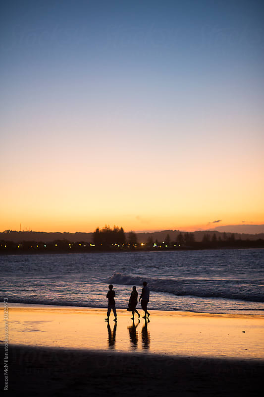 Walking along the beach at sunset by Reece McMillan for Stocksy United