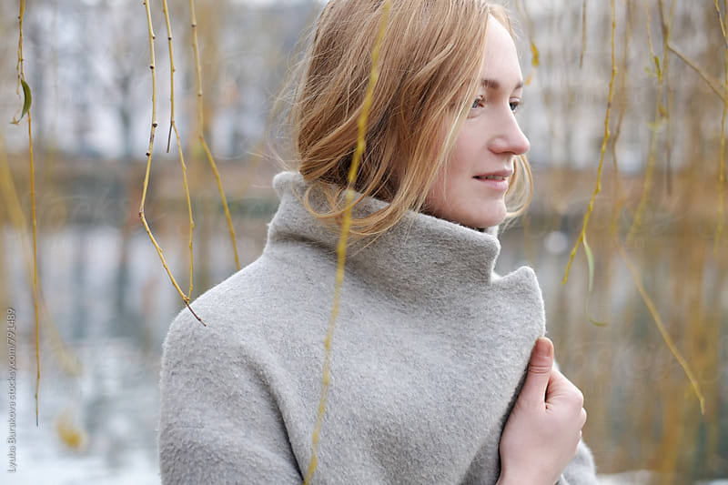 Blonde woman wrapped in a coat by Lyuba Burakova for Stocksy United