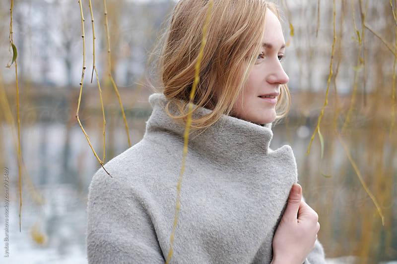 Blonde woman wrapped in a coat by Liubov Burakova for Stocksy United