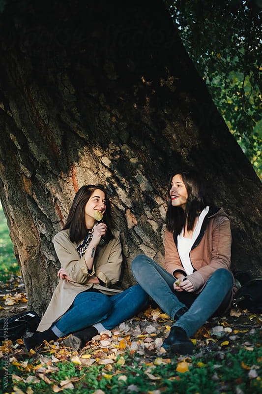 Two beautiful female friends having a good time outdoors by Marija Mandic for Stocksy United
