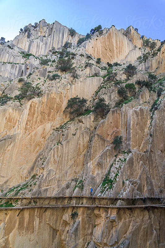 Climber walking on wooden walkway at the edge of a cliff in Caminito del Rey by ACALU Studio for Stocksy United