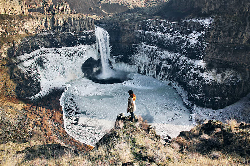 Woman standing on rock in front of Winter waterfall by Tari Gunstone for Stocksy United