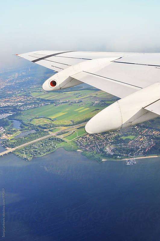 view from an airplane flying over the sea by Sonja Lekovic for Stocksy United