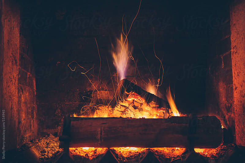 Sparking fire in fireplace by Shelly Perry for Stocksy United