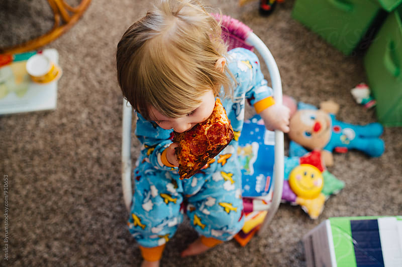 Little girl has pizza for breakfast by Jessica Byrum for Stocksy United