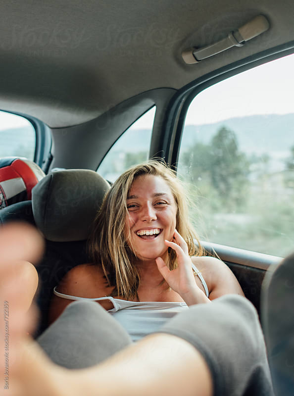 Woman driving in back of the car  by Boris Jovanovic for Stocksy United