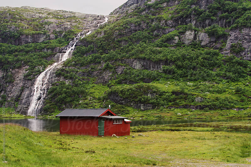 Red wooden cabin in a green valley with a sunlit waterfall in the background by Kaat Zoetekouw for Stocksy United