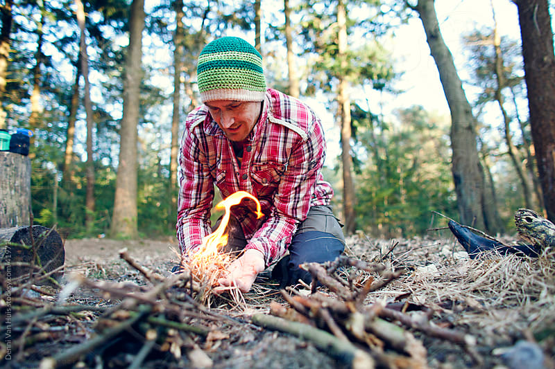 Man starting a camp fire in a forest by Denni Van Huis for Stocksy United