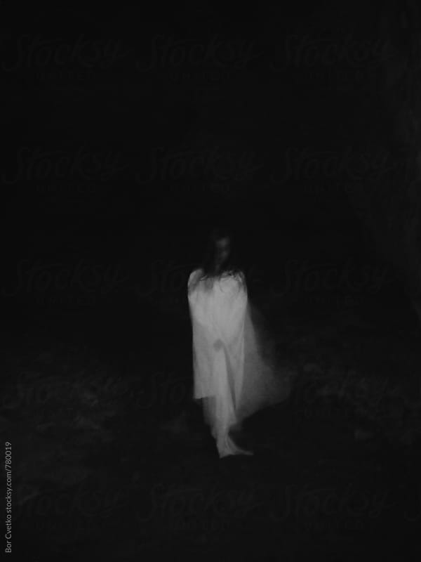 Girl in white dress in the dark by Bor Cvetko for Stocksy United