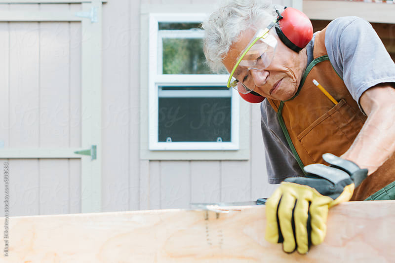 Elderly woman carpenter cutting lumber with a hand saw by Mihael Blikshteyn for Stocksy United