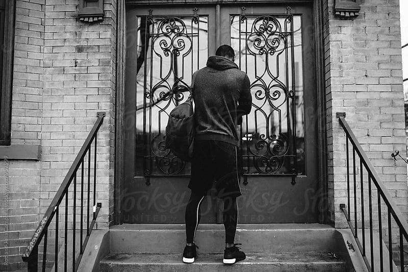 Young black man leaving home for morning workout by Rob and Julia Campbell for Stocksy United
