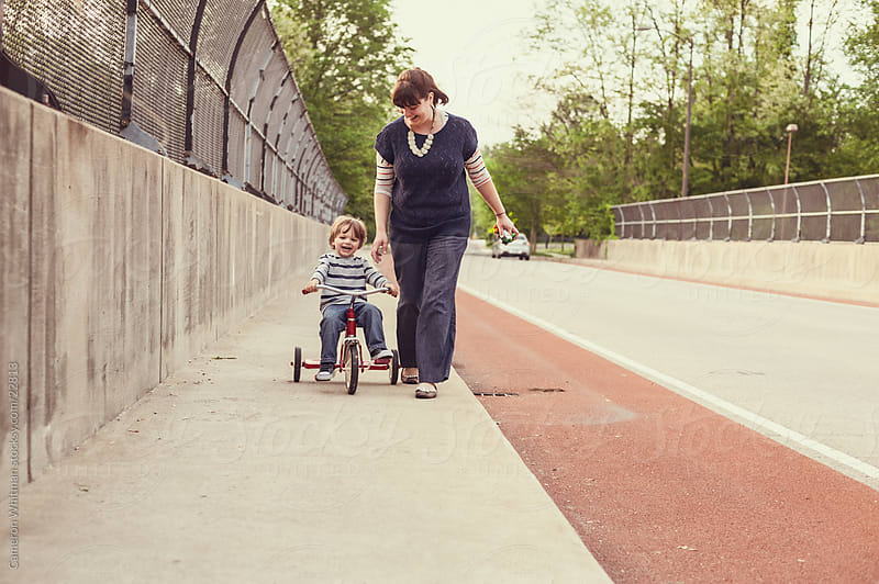 Mother Teaching Son To Ride A Tricycle by Cameron Whitman for Stocksy United