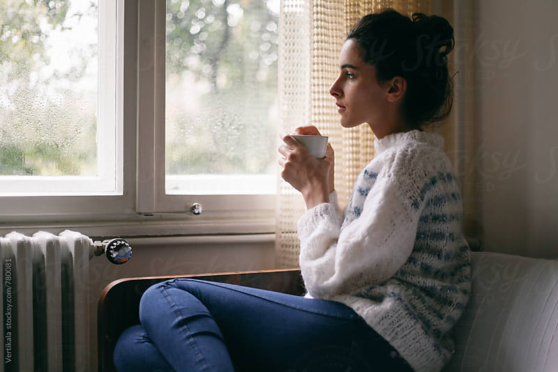Beautiful woman holding a cup of tea sitting near a window  by Marija Mandic for Stocksy United