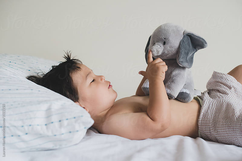 Little kid playing with stuffed animal by Lauren Naefe for Stocksy United