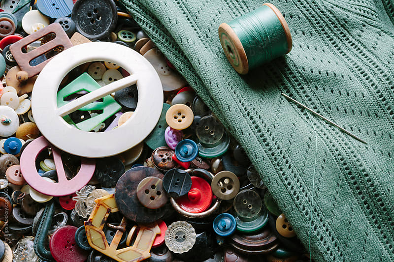 Collection of antique and vintage buttons and buckles, green cardigan being repaired by Paul Phillips for Stocksy United