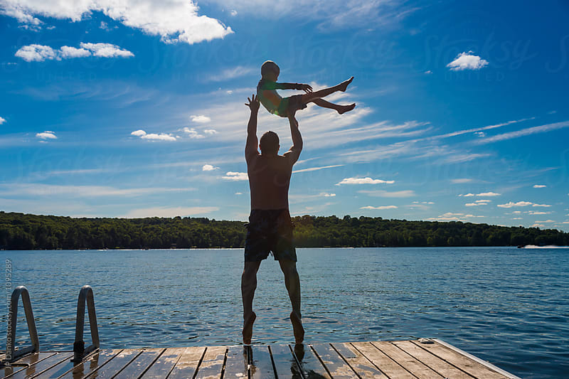 Father Throwing Son Into Warm Summer Cottage Lake from Dock by JP Danko for Stocksy United