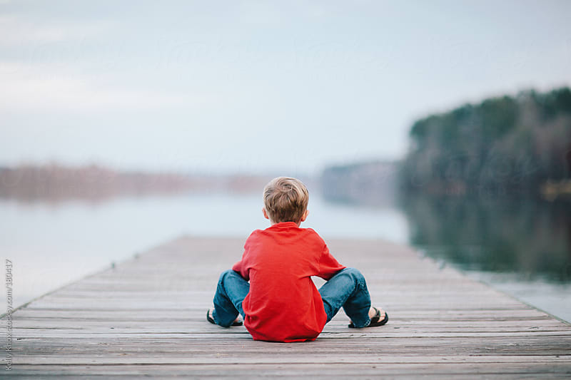 boy relaxing on a pier by Kelly Knox for Stocksy United