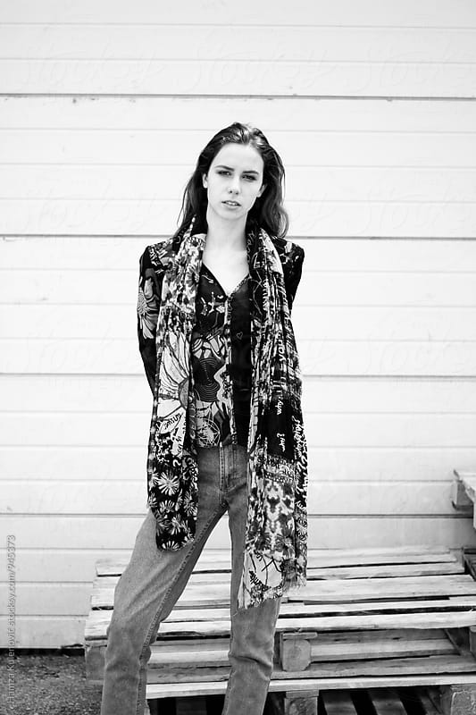 Black and white photo of a girl in interesting pattern clothes by Hamza Kulenović for Stocksy United
