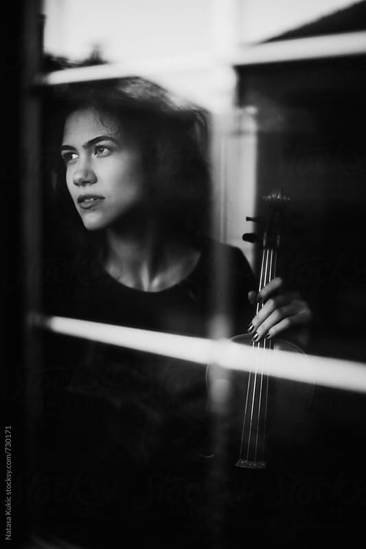 Portrait of a young girl with a violin looking through the window by Natasa Kukic for Stocksy United