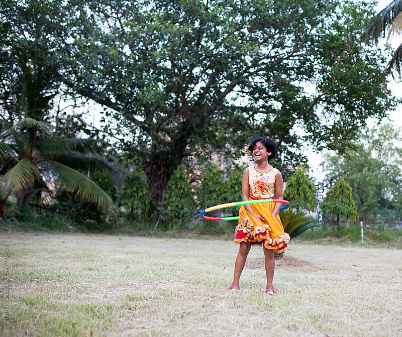 A girl playing with Hula Hoop in outdoor by PARTHA PAL for Stocksy United